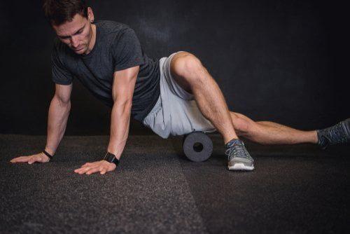 homme sportif pratiquant des automassages sur sa jambe avec un rouleau