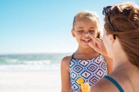 jeune fille qui se fait mettre de la crème solaire sur le nez