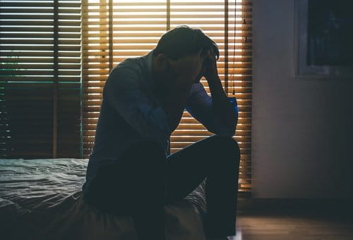 homme victime de dépression assis au bord de son lit