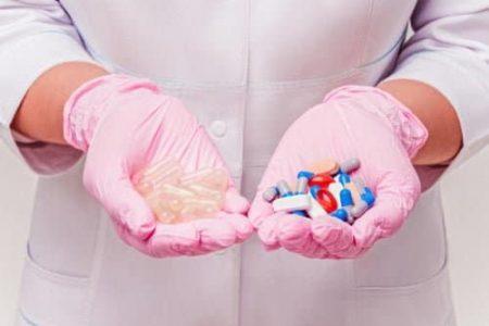 deux mains avec des gants roses présentant des gélules vides ou des gélules colorées