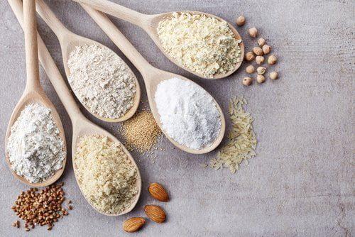 cinq cuillères en bois contenant des fariens sans gluten (amandes, amarante, sarrasin, pois chiche, riz)