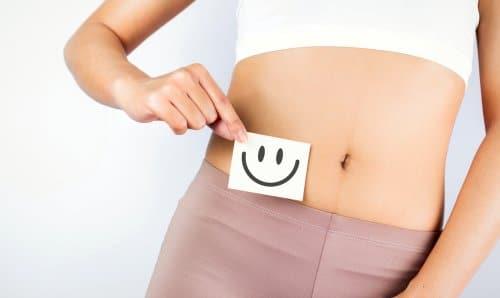 ventre de jeune femme avec un smiley souriant dessiné sur un papier
